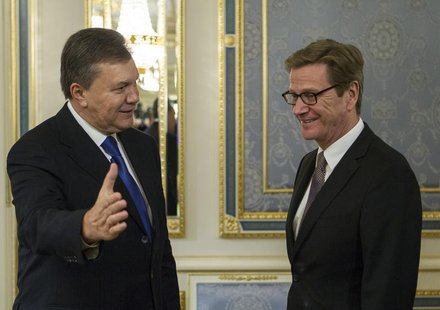 Ukrainian President Viktor Yanukovich (L) welcomes German Foreign Minister Guido Westerwelle during their meeting in Kiev October 10, 2013.