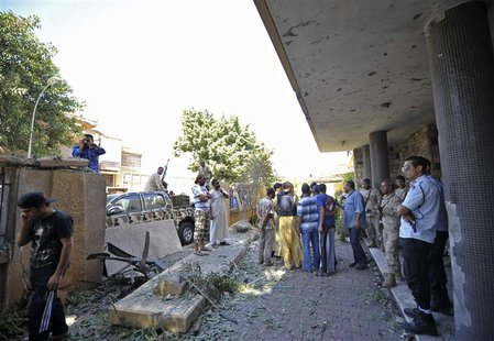 Security personnel and residents gather at the scene of a car bomb explosion at the Swedish consulate in Benghazi October 11, 2013. REUTERS/