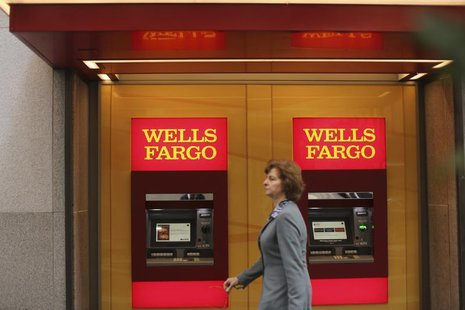 A woman walks past teller machines at a Wells Fargo bank in San Francisco, California October 10, 2013. REUTERS/Robert Galbraith