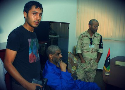 Muammar Gaddafi's former spy chief Abdullah al-Senussi (C) is seen in custody in Tripoli in this undated handout picture. REUTERS/Libyan Nat