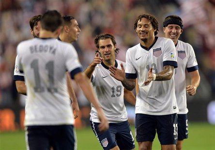 Oct 11, 2013; Kansas City, KS, USA; United States midfielder Graham Zusi (19) celebrates with his teammates after scoring against Jamaica du