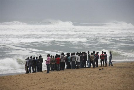 People watch as waves from the Bay of Bengal approach the shore at Podampata village in Ganjam district, in the eastern Indian state of Odis
