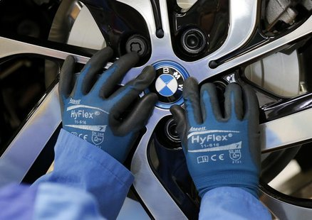 A worker mounts the logo on a rim at the serial production BMW i3 electric car in the BMW factory in Leipzig September 18, 2013. REUTERS/Fab