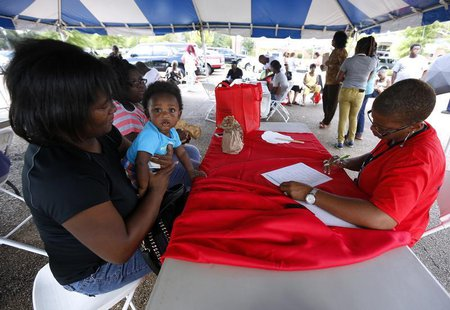 Lisa Smith (R) helps uninsured Danielle Winters (L) and her 7-month-old grandson Tyler, who is on medicare, sign up for the Affordable Care
