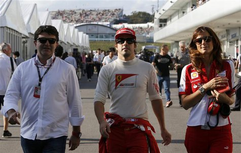 Ferrari Formula One driver Fernando Alonso (C) of Spain walks in the paddock with his agent Luis Garcia Abad (L) and his press officer Rober