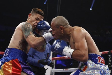 Featherweight boxer Orlando Cruz (L) of Puerto Rico takes a punch from Orlando Salido of Mexico during their title fight at the Thomas and M
