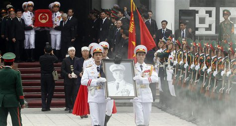 Soldiers hold up the portrait of the late General Vo Nguyen Giap as his coffin is carried during his funeral at the National Funeral House i