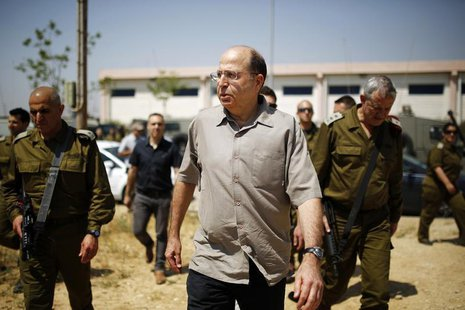 Israeli Defense Minister Moshe Yaalon (C) walks next to Israel's armed forces chief Major-General Benny Gantz (R) during a visit to a milita