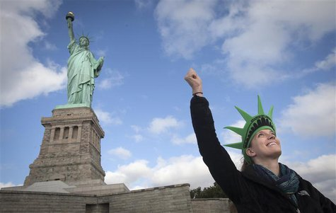 Bethany McNew, 24, from Tampa, mimics the pose of the Statue of Liberty as she poses for a photo on Liberty Island in New York, October 13,