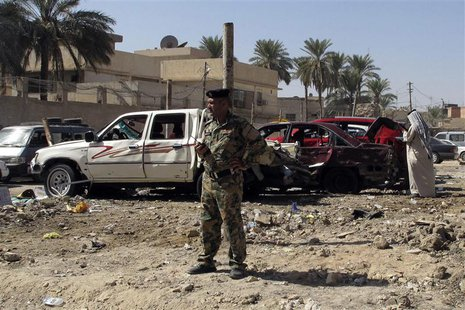 An Iraqi security forces member stands at the site of a car bomb attack in the city of Hilla, 100 km (60 miles) south of Baghdad, October 13