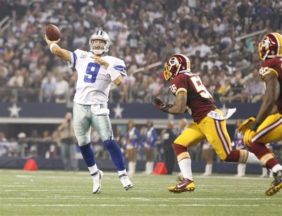 Oct 13, 2013; Arlington, TX, USA; Dallas Cowboys quarterback Tony Romo (9) throws a touchdown pass while being rushed by Washington Redskins
