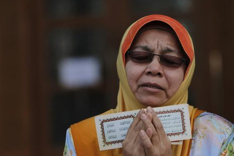 A Muslim woman recites a prayer during a demonstration outside Malaysia's Court of Appeal in Putrajaya, outside Kuala Lumpur October 14, 201