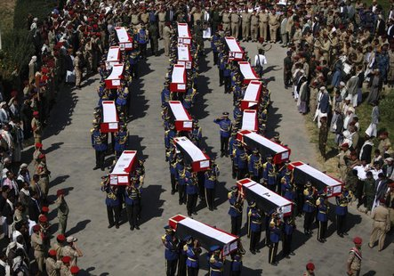 Honour guards carry the coffins of soldiers and policemen killed in recent attacks during a funeral procession in Sanaa September 22, 2013.
