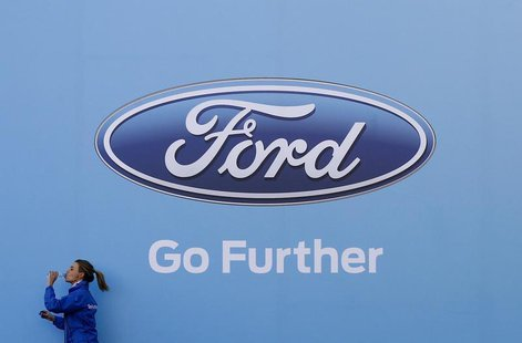 A woman has a drink as she walks past a logo of carmaker Ford at the entrance to a media event for the launch of a concept car in Sydney Aug