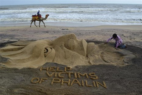 Indian sand artist Sudarshan Pattnaik works on a sand sculpture about Cyclone Phailin that hit Puri in the eastern Indian state of Odisha Oc
