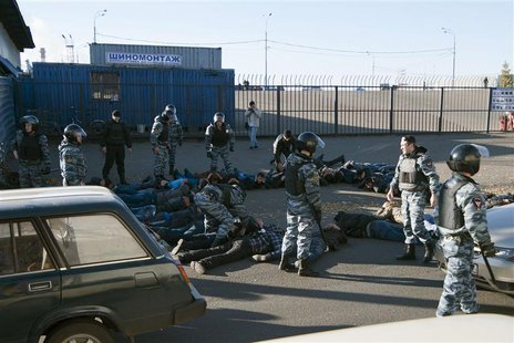 Russian police detain migrant workers during a raid at a vegetable warehouse complex in the Biryulyovo district of Moscow October 14, 2013.