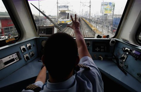 A train operator on Southeast Asia's first light rail transit (LRT) network, which is 29-years-old, signals to a colleague in another train