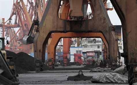 Stevedores walk under giant cranes as they wait to load coal imported from North Korea onto trucks at Dandong port in the Chinese border cit