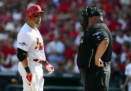 Oct 4, 2013; St. Louis, MO, USA; St. Louis Cardinals right fielder Carlos Beltran (left) argues with home plate umpire Wally Bell (right) af