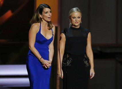 Actresses Tina Fey (L) and Amy Poehler present the award for Outstanding Supporting Actress In A Comedy Series at the 65th Primetime Emmy Aw