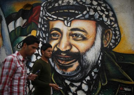 Palestinians walk past a mural depicting late Palestinian leader Yasser Arafat in Gaza City November 27, 2012. REUTERS/Suhaib Salem