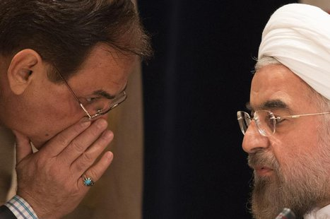 A member of Iran's delegation speaks to Iran's President Hassan Rouhani (R) before a news conference in New York September 27, 2013. REUTERS