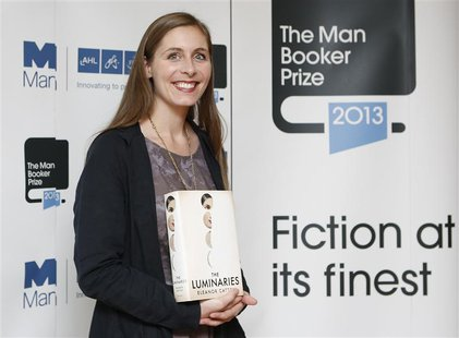 "Man Booker prize shortlist nominee Eleanor Catton poses with her book ""The Luminaries"" during a photocall at the Southbank Centre in London,"