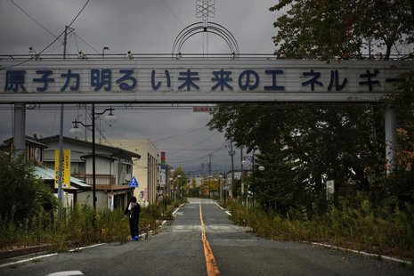 "A woman, who came for a brief visit to her home, walks under a sign reading ""Nuclear Power - The Energy for a Better Future"", at the entranc"
