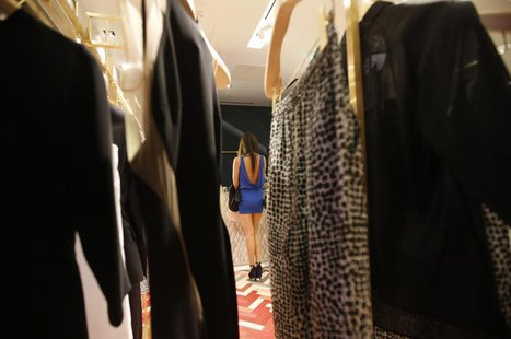 A woman pays for her purchases at a fashion accessory shop at a foreign luxury brand's boutique in Beijing May 21, 2013. REUTERS/Kim Kyung-H