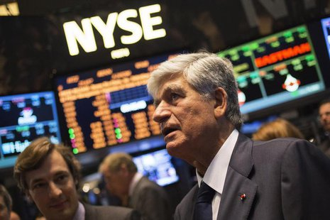 Publicis Group Chairman and CEO Maurice Levy (R) watches a stock ticker after announcing an agreement on their merger on the floor of the Ne