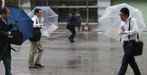 Men struggle against strong wind and rain caused by approaching Typhoon Wipha at a business district in Tokyo October 16, 2013. REUTERS/Toru