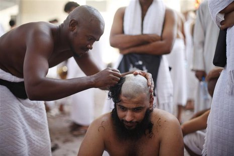 A Muslim pilgrim has his head shaved after casting pebbles at a pillar that symbolizes Satan during the annual haj pilgrimage, on the first