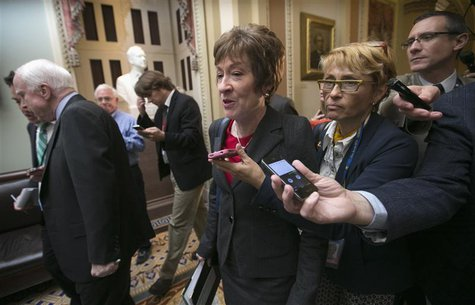 Senator Susan Collins (R-ME) is trailed by reporters as she walks with Senator John McCain (R-AZ) in the U.S. Capitol in Washington October