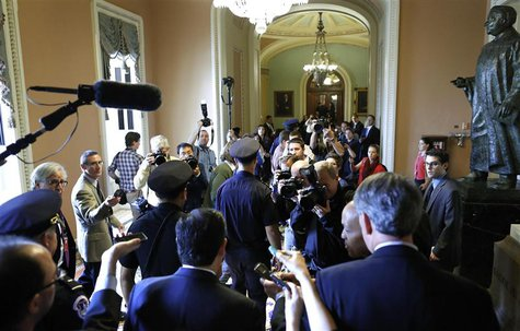 U.S. Senator Ted Cruz (R-TX) (bottom C) is flanked by reporters and police as he departs after a Republican Senate caucus meeting at the U.S