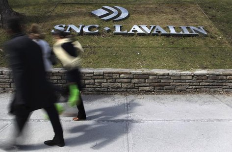 Pedestrians walk past a sign for the head office of SNC Lavalin in downtown Montreal March 26, 2012. REUTERS/Christinne Muschi