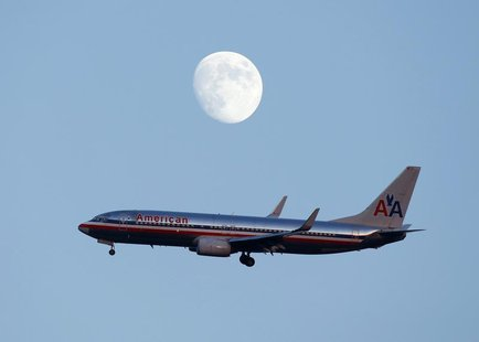 An American Airlines passenger jet glides in under the moon as it lands at LaGuardia airport in New York, August 28, 2012. REUTERS/Eduardo M