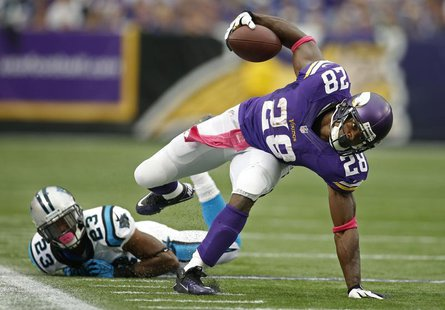 Oct 13, 2013; Minneapolis, MN, USA; Minnesota Vikings running back Adrian Peterson (28) breaks the tackle of Carolina Panthers cornerback Me