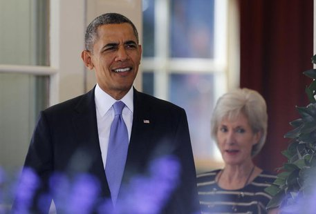 U.S. President Barack Obama walks out to deliver remarks alongside Human Services Secretary Kathleen Sebelius (R) and other Americans the Wh