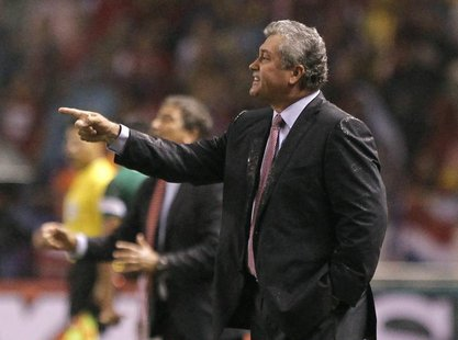 Mexico's coach Victor Manuel Vucetich (R) gives instructions to his players during their 2014 World Cup qualifying soccer match against Cost