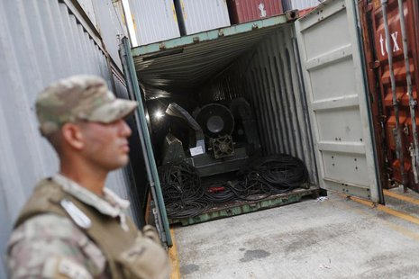 "A police officer stands guard at a container holding arms seized from the North Korean flagged ship ""Chong Chon Gang"" at the Manzanillo Cont"