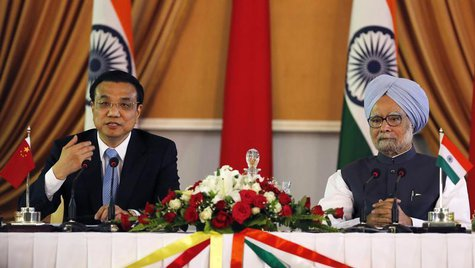 Chinese Premier Li Keqiang (L) speaks with the media as India's Prime Minister Manmohan Singh looks on during the signing of agreements cere