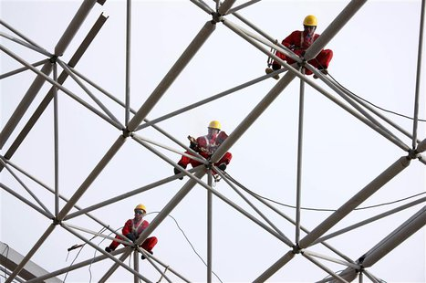 Workers set up scaffolding at a construction site in Huaibei, Anhui province, October 16, 2013. REUTERS/Stringer