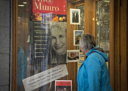 A customer looks at a window display congratulating Canadian author Alice Munro at bookstore Munro's Books after she won the Nobel Prize for