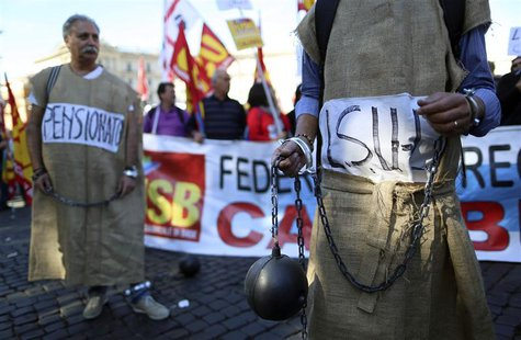 Demonstrators dressed to represent prisoners, hold chains and a mock cannonball during a protest against the reforms by the Italian governme