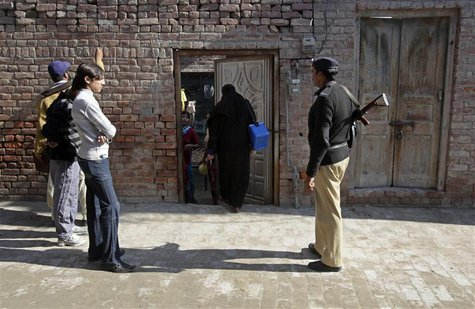 A policeman stands guard as female polio workers wait to give polio vaccine drops to children in Lahore December 20, 2012. REUTERS/Mohsin Ra