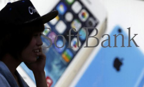 A pedestrian using a mobile phone walks past a shop window of Japan's mobile phone operator Softbank in Tokyo, September 20, 2013. REUTERS/Y