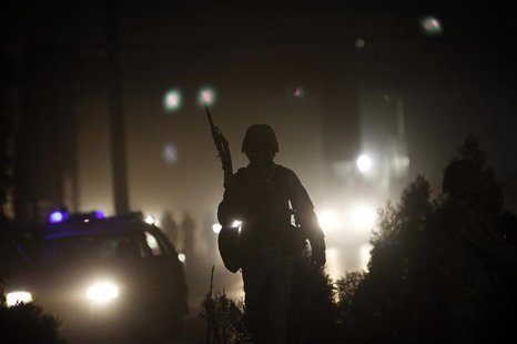 An Afghan policeman keeps watch at the site of an attack in Kabul October 18, 2013. REUTERS/Omar Sobhani