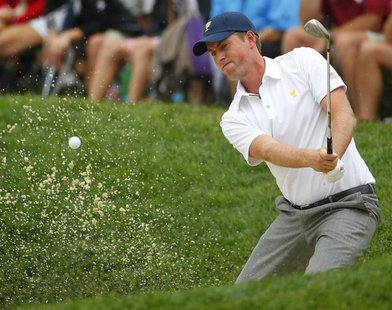 U.S. team member Webb Simpson hits from a bunker on the 14th hole as he plays International player Louis Oosthuizen of South Africa during t