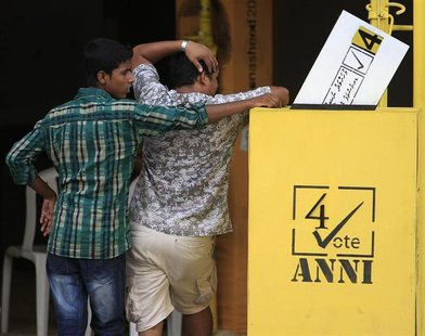 Men stand next to a dummy model of a ballot box, promoting the election campaign of Maldivian presidential candidate Mohamed Nasheed, outsid
