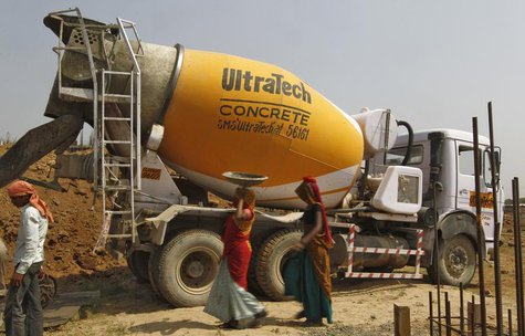 Workers walk in front of an UltraTech concrete mixture truck at the construction site of a commercial complex on the outskirts of the wester